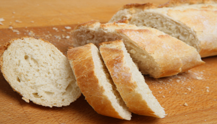 Rustic white bread baguette cut into slices.